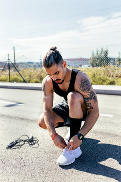 Sporty young man tying shoes before training on a road