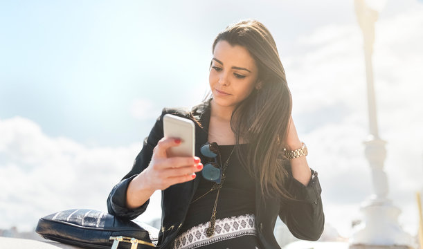 Young beautiful woman sending a message with the smartphone on the beach