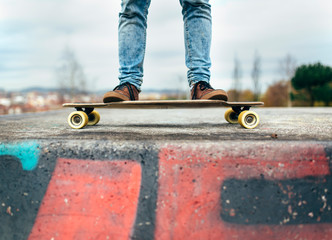 Legs of young man standing on his skateboarder