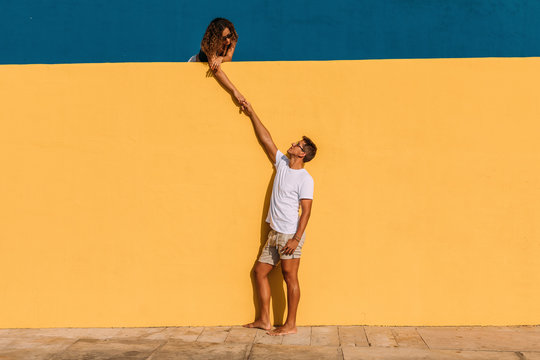 Young man and woman behind a yellow wall holding hands