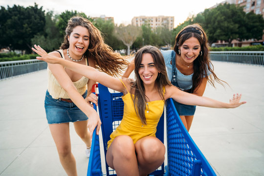 Three playful female, friends with shopping cart in the city