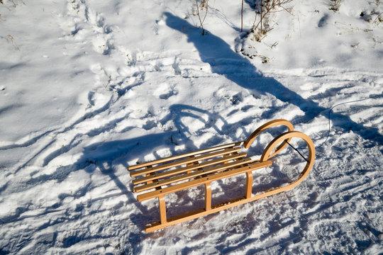 Germany, North Rhine-Westphalia, Eifel, shadow of person next to sledge in winter landscape