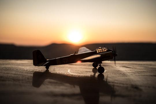 World war ii fighter plane at sunset or dark orange fire explosion sky. War scene. German figher at sky. Selective focus