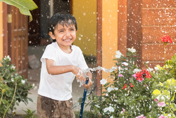 Child plays with water while watering the garden