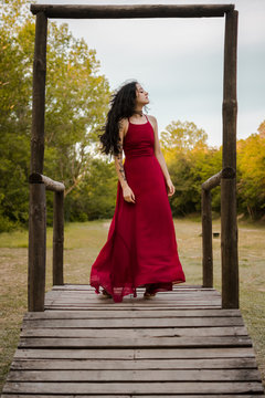 Young woman in a red dress on a wooden platform