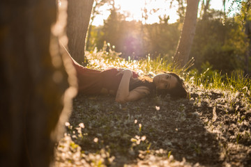 Young woman poses in a forest at sunset