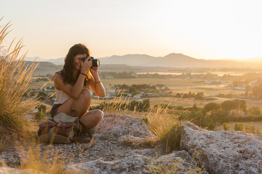 Young woman taking a picture with her camera on top of a mountain