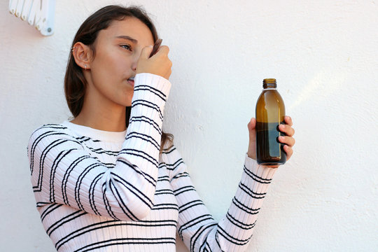 Young woman taking a cough syrup