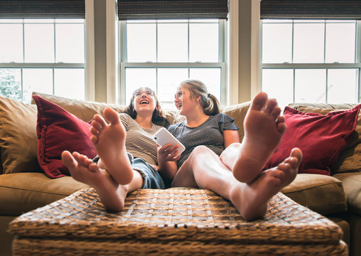 Two teenage girls with phone sitting on couch with feet up laughing