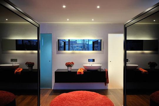 Modern bathroom in contemporary house with dark closet