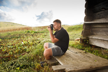 Man in black t-shirt takes pictures of mountain scenery