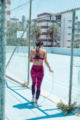 Colorful image of female athlete walking on court with jumping rope