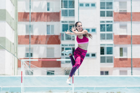 Colorful image of full body of female athlete jumping on court