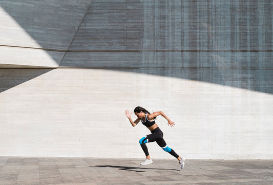Pulled back view of female athlete running on concrete vertical