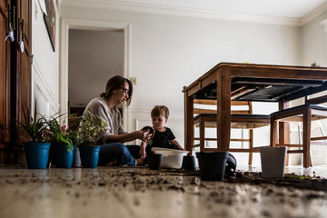 Mother and young son sit on kitchen floor with plants and dirt