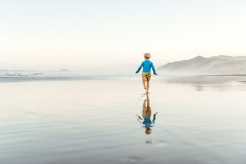Toddler boy running on a beach with reflection