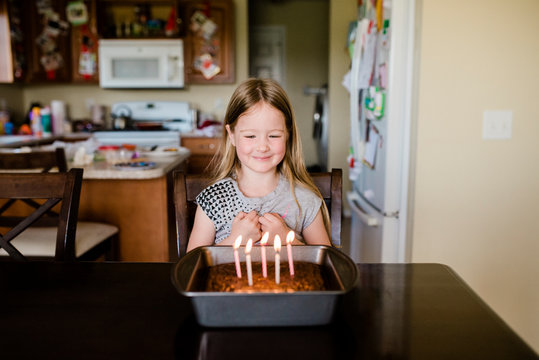 5 year old girl smiles at birthday candles on a cake in kitchen