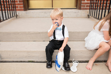 Ring bearer baby sits next to flower girl on steps and looks at camera
