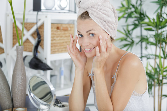 woman checking her wrinkles in the mirror