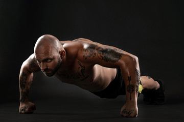 Athletic bald, tattooed man in black shorts and sneakers is posing against a black background. Close-up portrait.