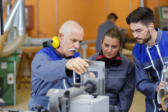 portrait of senior laborer with apprentices