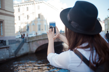 Tourist in the city takes a photo on smartphone. A young woman in a black hat and a white shirt,