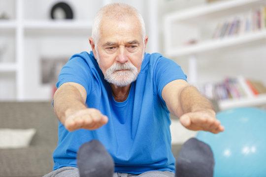 sporty elderly guy practicing yoga indoors