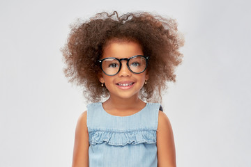 childhood, school and education concept - happy little african american girl in glasses over grey...