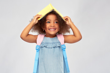 childhood, school and education concept - happy little african american girl with book and backpack over grey background