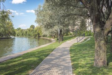 Photo sur Plexiglas Kaki Walkway in the park along the river. Beautiful landscape of summer.