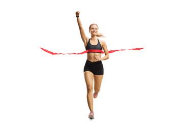 Young female runner on the finish line of a marathon gesturing happiness