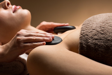 wellness, beauty and relaxation concept - close up of young woman having hot stone massage at spa