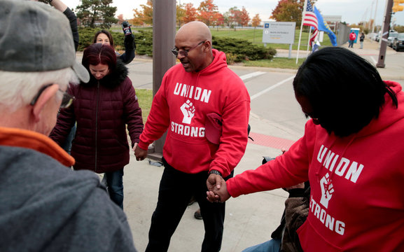 Striking United Auto Worker (UAW) Joe Ryan leads a prayer circle on the picket line outside the General Motors Detroit-Hamtramck Assembly in Hamtramck