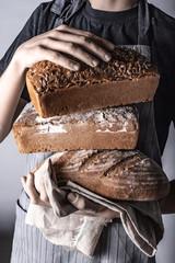 Trzymanie różnych rodzajów chleba w dłoniach na szarym tle w stylu rustykalnym przez osobę w fartuchu