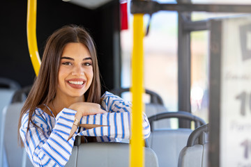 Portrait of a woman inside a bus. Beautiful young woman taking bus to work. Woman riding in a bus and looking happy. Young woman riding in public transport. Woman travelling by bus
