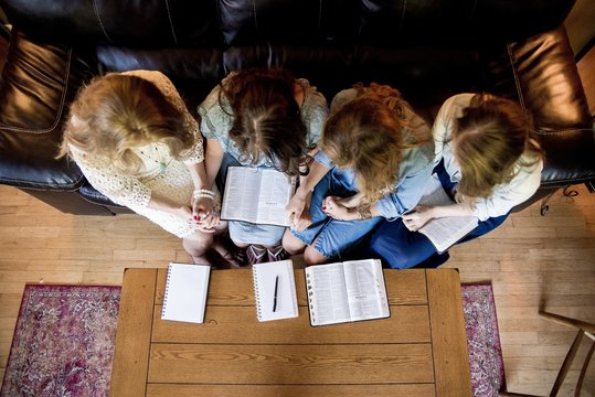 Overhead shot of females sitting while holding hands and reading the bible