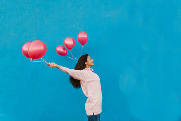 Happy girl with balloons, outdoors Wall mural