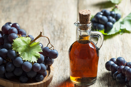 Glass bottle of organic black grape balsamic vinegar made from fermented fresh grapes. Healthy organic food black fruit, selective focus