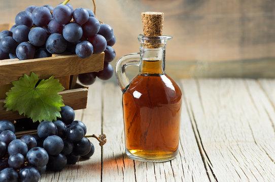 Glass bottle of organic black grape balsamic vinegar made from fermented fresh grapes. Healthy organic food black fruit, selective focus
