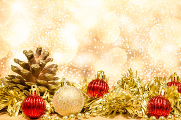 Background christmas or new year. Christmas decorations in gold and red balls and gold gift bow with tree decorations. Light bokeh background.