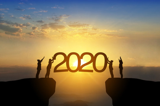Silhouette image of happy teamwork standing on opposite sides of cliff use their hand push 2020 text to the sky like as set up year 2020 target.