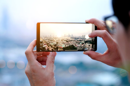 Young people take pictures of the buildings in the city. Sunrise time He uses a high-angle recording photo phone.Travel concepts and technology