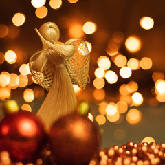 Christmas ornaments and straw angel lying on balls of a Christmas chain on a blurred background with lights.
