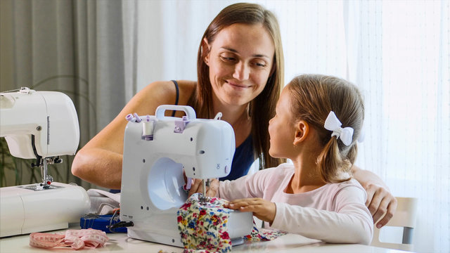 A girl is using a small sewing machine, a woman using a needle. A mother and a daughter are at home together, day time. Mommy explains a little child how to work with equipment and fabric. Close-up.