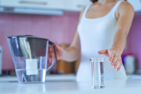 Drinking woman drinks clear purified water from a water filter in the morning in the kitchen at home. Healthy lifestyle