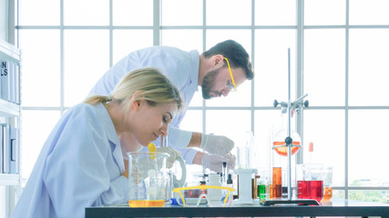 group of people scientist holding a tube with liquid substance. Man and woman Research is working in the Laboratory with foreground of tube and Beaker of liquid substance.