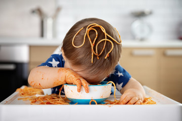 Funny baby falling asleep in bowl of spaghetti