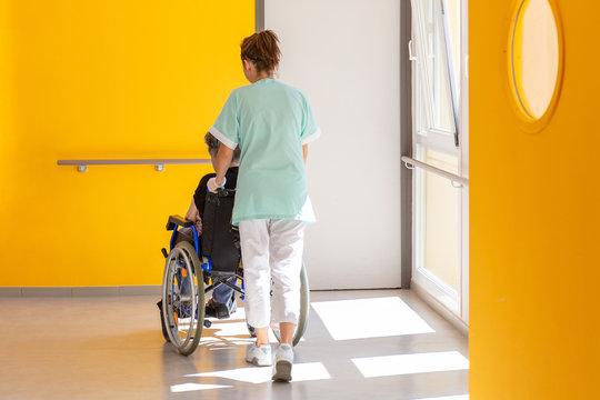 Soignante accompagne personne agée en fauteuil roulant