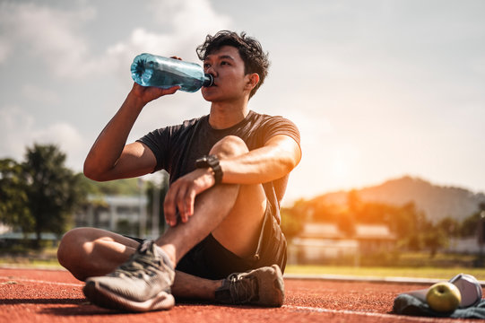 The young man wore all parts of his body and drink water to prepare for jogging on the running track around the football field.