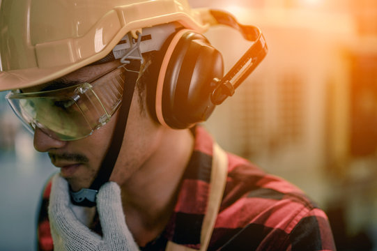 young engineer wearing a safety helmet Glasses and earphones are prepared to be working that require safety for safety at industrial plants. Engineering and architecture for factory industry concept.